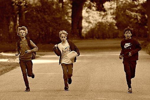 3人のティーンエイジャーが横並びでかけてくるセピア調の画像