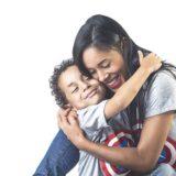 座った笑顔の母親にしがみついて微笑みを浮かべる男の子