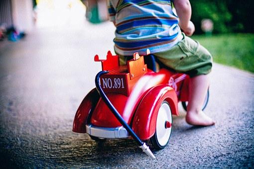 おもちゃの自動車にまたがった幼児の後ろ姿