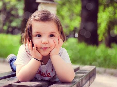 公園のベンチに寝転びいたずらな表情で頬杖をつく幼い女の子