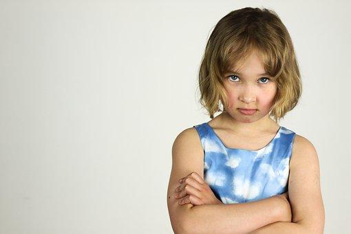 納得がいかない表情で腕組みをしてこちらを上目遣いで睨んでいる7歳くらいの少女