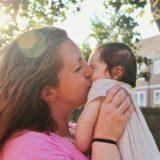 抱き上げた赤ちゃんの頰にキスする日常風景の中の母親