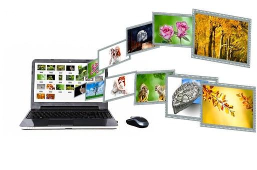 ノートパソコンにたくさんの画像が連なって取り込まれて行くイメージ画像