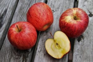 丸ごとのリンゴ3つと半割りのリンゴがひとつ床に落ちている