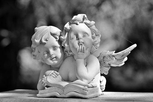 寝そべって本を読む二人の天使の石像