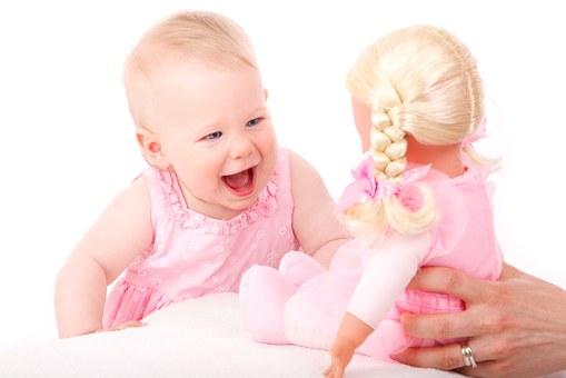 人形であやされて嬉しそうに笑う乳児