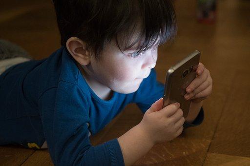 薄暗い部屋の中で明るいスマホの画面を食い入るように見つめる幼い男の子