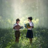 深い森の中で立ったまま本を読む制服姿の少年少女2名