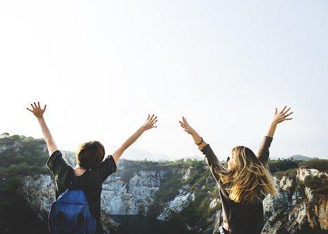 高い山の頂から両手を上げて遠くを見渡す2人の若者