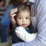 不安そうに親の胸にしがみつく生後半年くらいの赤ちゃん