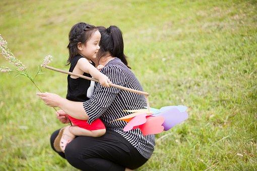 草原にしゃがみこんだ母の膝に抱かれて笑顔を浮かべる風車を持った少女